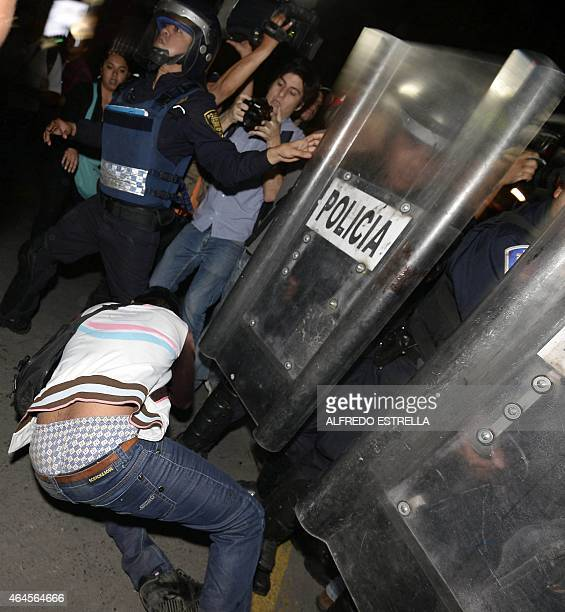 A student falls in front of a police line during a protest in Mexico City on February 26 as they demand justice and clarification for the...
