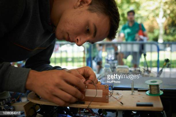A student finalizes his robot car A robots race took place in Toulouse Machines are either cars or walking robots They were supposed to run a 110...