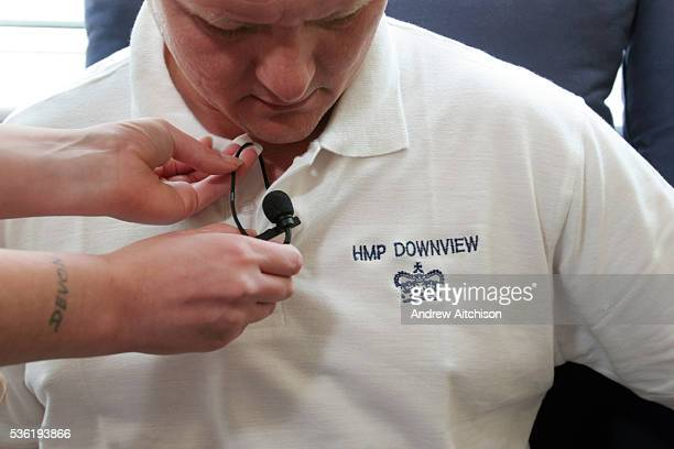 A student fitting a radio microphone to one of the prison guards at HMP Downview during a media training session HM Prison Downview is a women's...