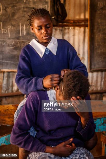 A student fix her friend's haircut Ngota's Upendo Primary School is a small school located in the heart of Mathare Slum Kenya's second biggest slum...