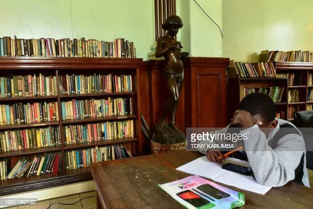 A student focuses on his studies next to to an antique bronze statuette inside the colonialera McMillan Memorial Library in the Kenyan capital...