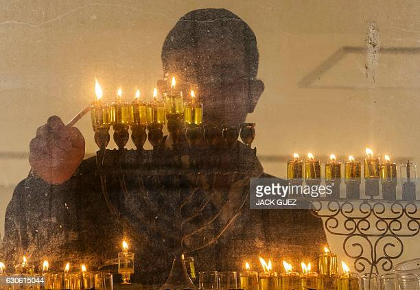 A student from a Yeshiva religious school lights a candle on a menorah during the Jewish holiday of Hannukah the festival of lights in the central...