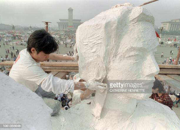 A student from an art institute plasters the neck of the Goddess of Democracy statue a replica of the New York Statue of Liberty on May 30 1989 in...