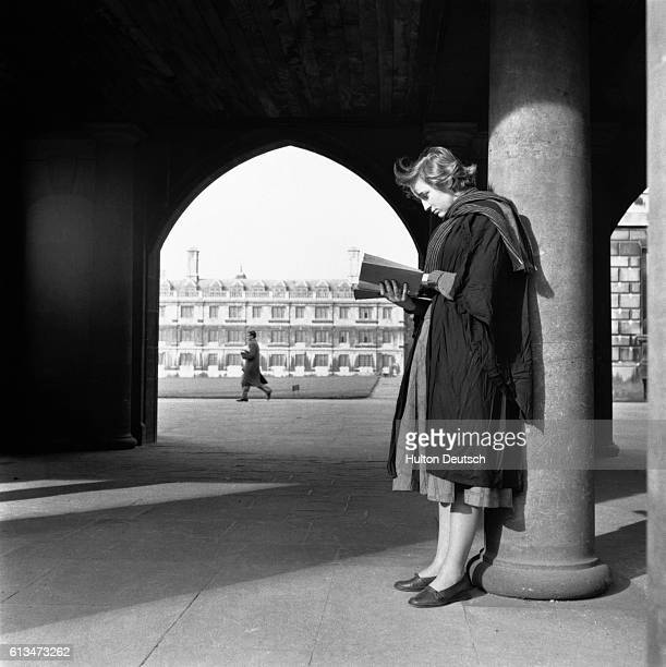A student from Cambridge University stands in front of an archway and reads | Location Cambridge Cambridgeshire England UK