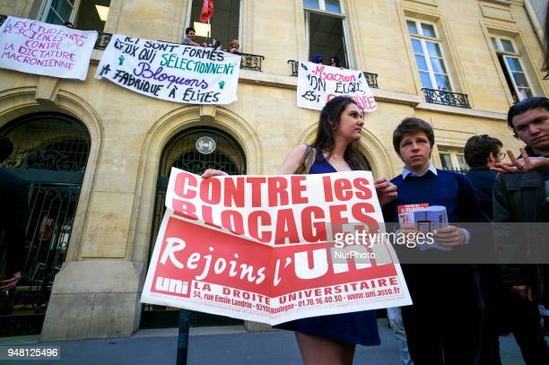 A student from rightwing party holds signs reading against the blockings as other students block the entrance of Sciences Po university on April 18...