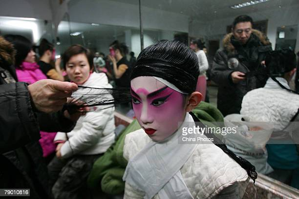 A student from the Peking Opera Department of the Jilin College of the Arts wears hairpiece with the help of his teacher on January 14 2008 in...