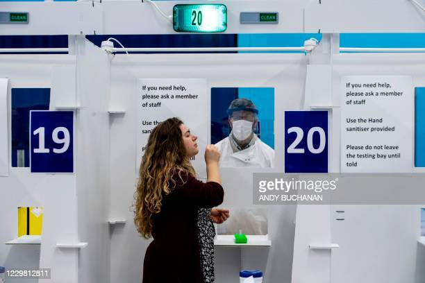 Student from the University of St. Andrews takes a swab for a lateral-flow test in a mass COVID-19 testing centre, set up in the University's sports...