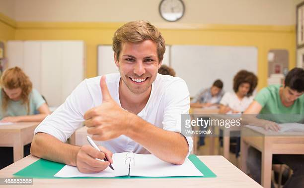 Student gesturing thumbs up at desk