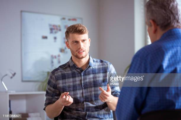 student gesturing while discussing with therapist - overworked stock pictures, royalty-free photos & images