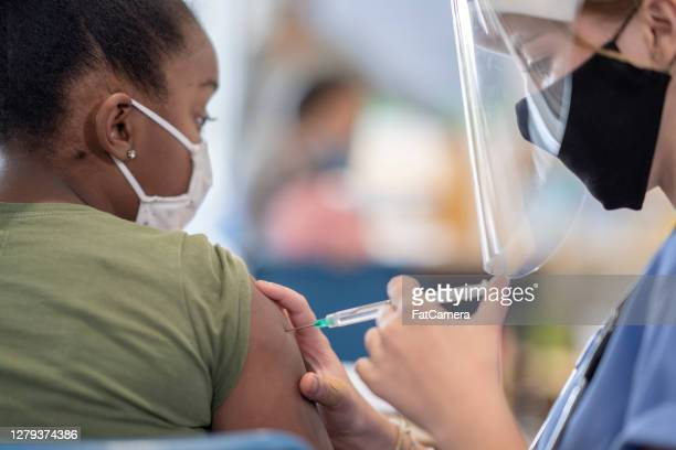 student getting vaccinated - fatcamera stock pictures, royalty-free photos & images