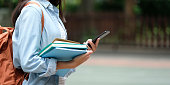 Student girl holding books and smartphone while walking in school campus background, education, back to school concept
