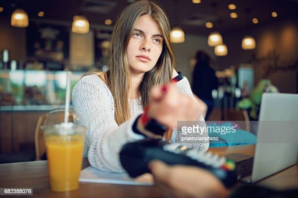 Student girl is paying her bill in cafeteria using her smart watch