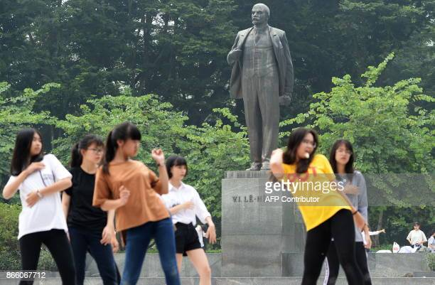 Student girls practice modern dance in front of a statue of Vladimir Lenin Russian communist leader at a public park in Hanoi on October 25 2017 /...