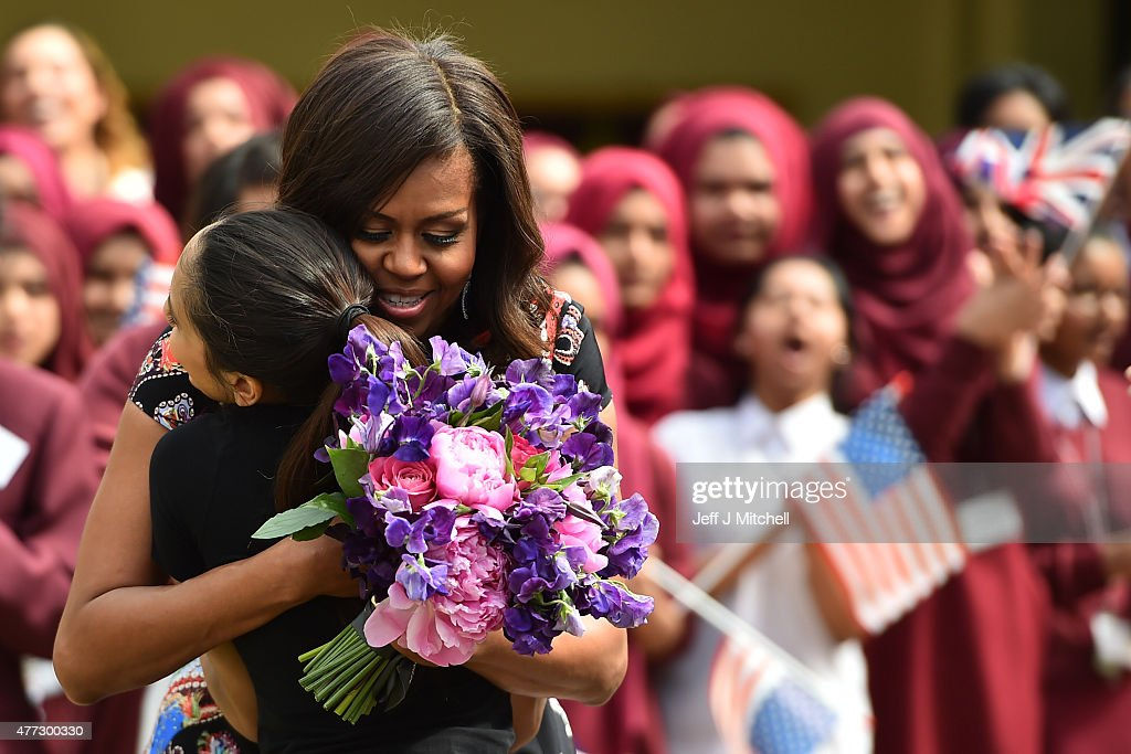 A student gives flowers to, embraces and welcomes with other young students US First Lady Michelle Obama in the courtyard before an event as part of the 'Let Girls Learn Initiative' at the Mulberry School for Girls on June 16, 2015 in London, England. The US First Lady is travelling with her daughters, Malia and Sasha and her mother, Mrs. Marian Robinson, to continue a global tour promoting her 'Let Girls Learn Initiative'. The event at the school was to discuss how the UK and USA are working together to expand girl's education around the world.