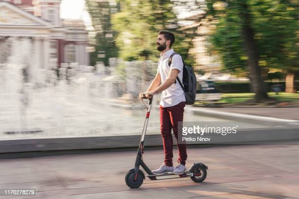 student going to school with his electric scooter - motor scooter stock pictures, royalty-free photos & images