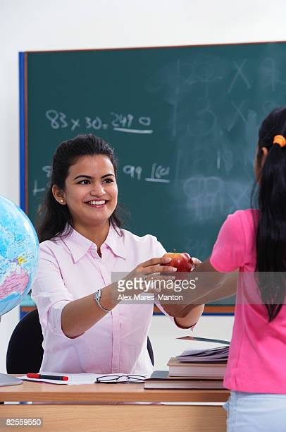 student handing apple to teacher