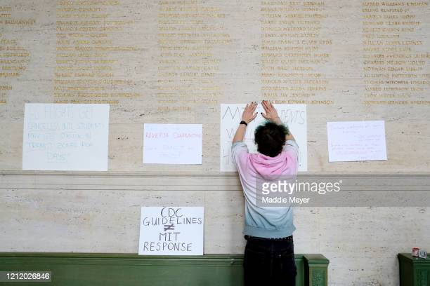 A student hangs signs to protest inside Building 10 on the campus of Massachusetts Institute of Technology on March 12 2020 in Cambridge...
