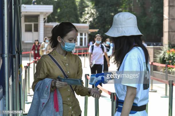 Student has her body temperature checked before entering a school to sit the National College Entrance Examination , known as Gaokao, in Nanjing, in...