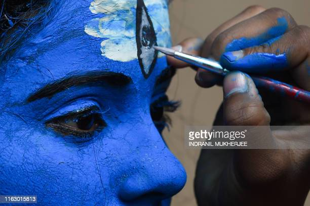 A student has her face painted to dress up as the Hindu god Lord Shiva for a cultural event in her school in Mumbai on August 21 2019