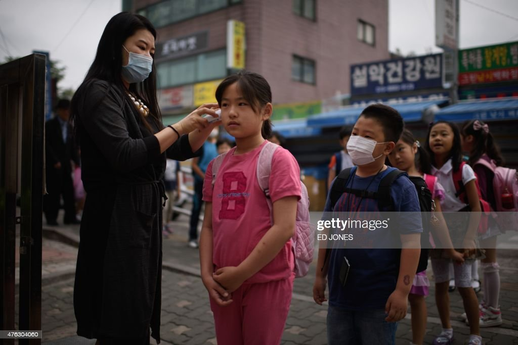 A student has her temperature taken by a teacher outside the Sungshin elementary school in Seoul on June 8, 2015. South Korea recorded its sixth death and biggest single day jump in Middle East Respiratory Syndrome (MERS) infections, with 23 new cases in the largest outbreak of the potentially deadly virus outside Saudi Arabia. AFP PHOTO / Ed Jones
