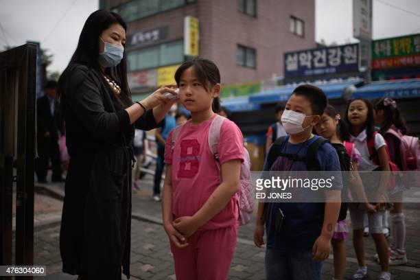 A student has her temperature taken by a teacher outside the Sungshin elementary school in Seoul on June 8 2015 South Korea recorded its sixth death...