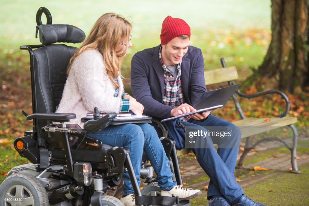 Student helping friend with disability : Stock Photo