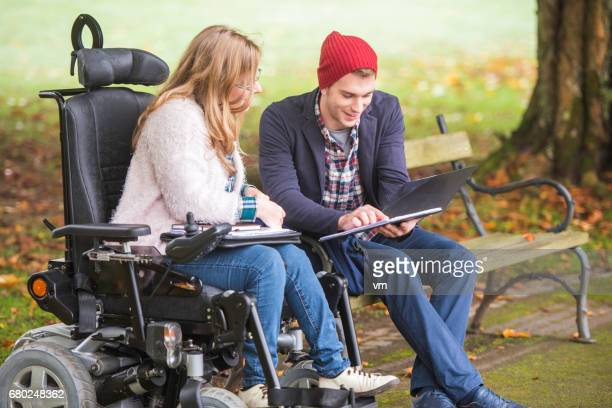 student helping friend with disability - disability stock photos and pictures