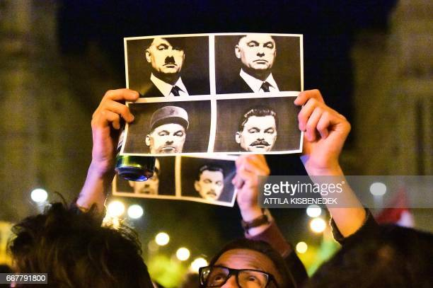 A student hold up a combo picture of three dictators Adolf Hitler Fidel Castro of Cuba and Joseph Stalin of Soviet Union with Hungarian Prime...