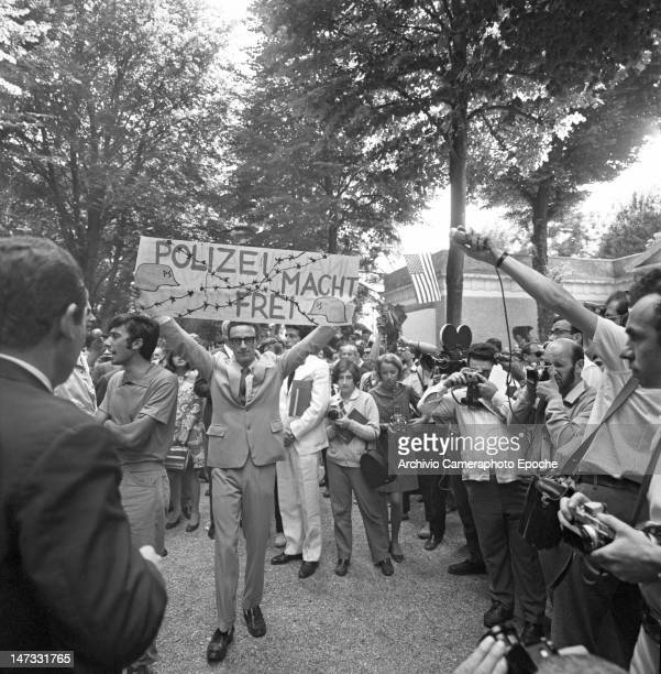 A student holding a banner saying 'Polizei Macht Frei' during the protest against the Biennale Giardini Venice 1968