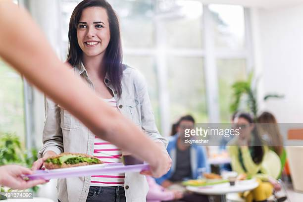 Student holding a tray in cafeteria.