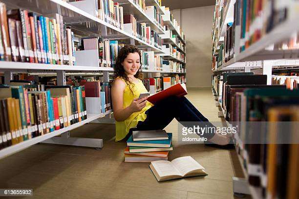 Student holding book and being distracted with mobile phone
