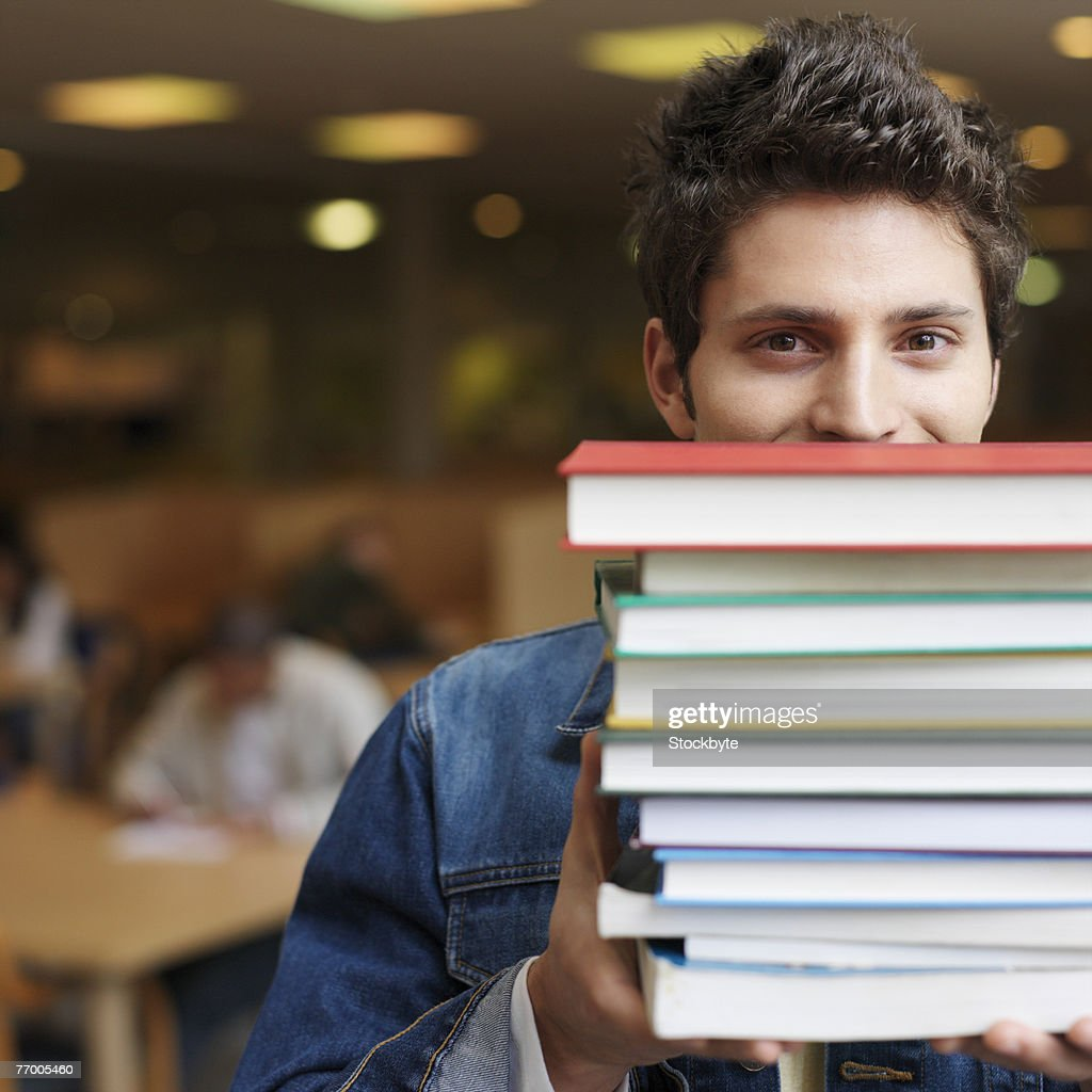 Student holding books in front of face in library, portrait : Stock Photo