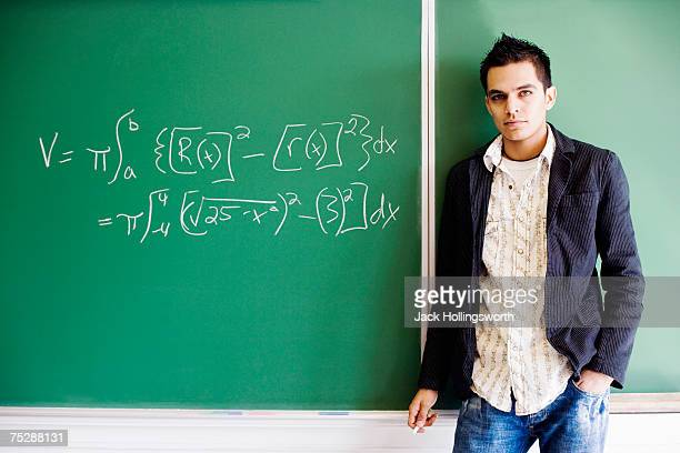 Student holding chalk in classroom, portrait