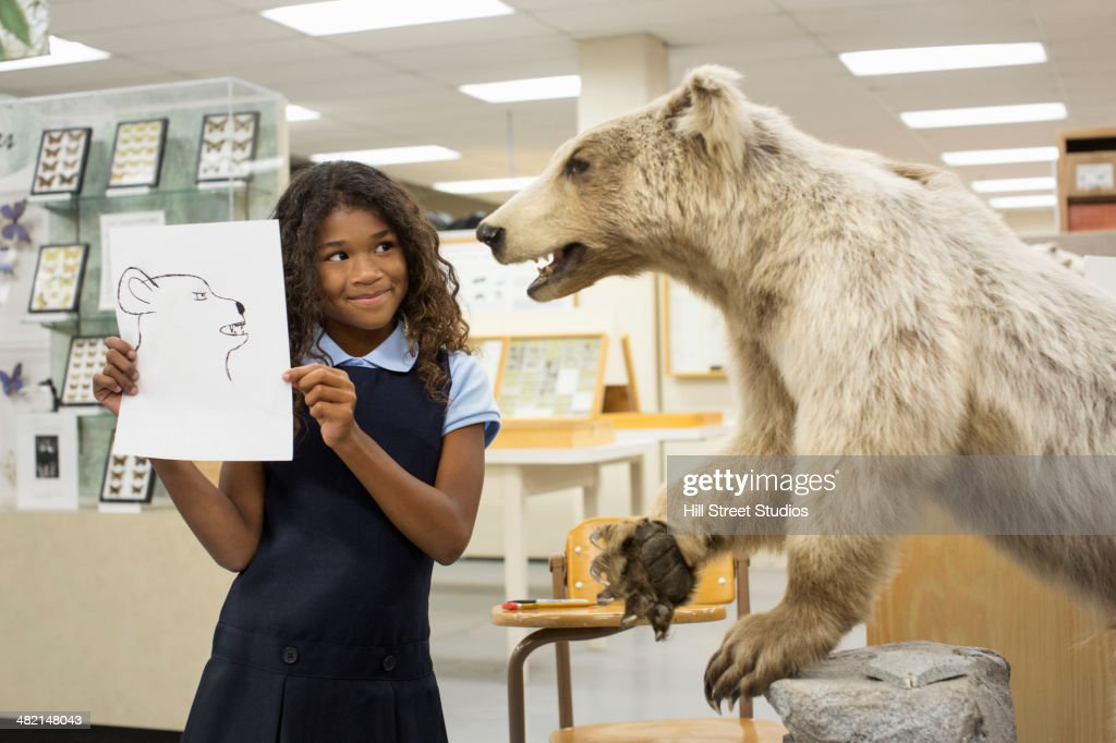 Student holding drawing of bear in museum : Stock Photo