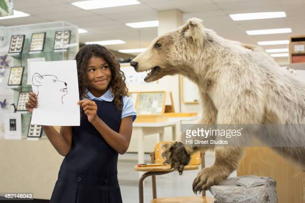 Student holding drawing of bear in museum
