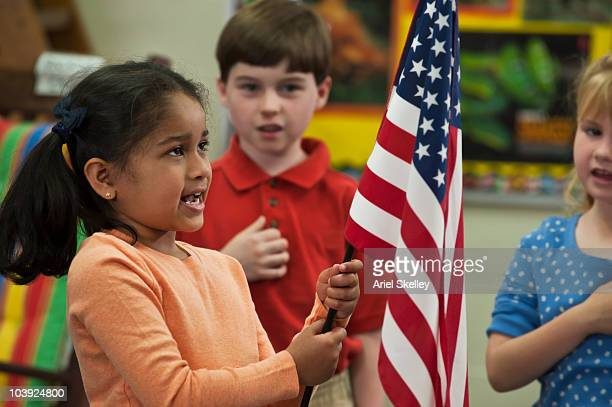 Student holding flag reciting Pledge of Allegiance