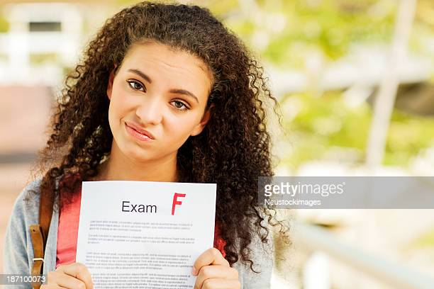 Student Holding Test Result With F Grade On Campus