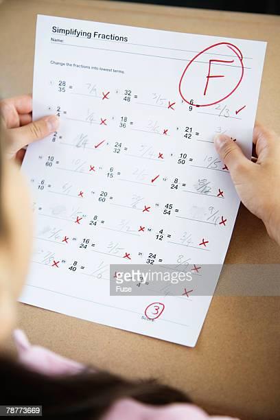 student holding test with f grade - miss f fotografías e imágenes de stock