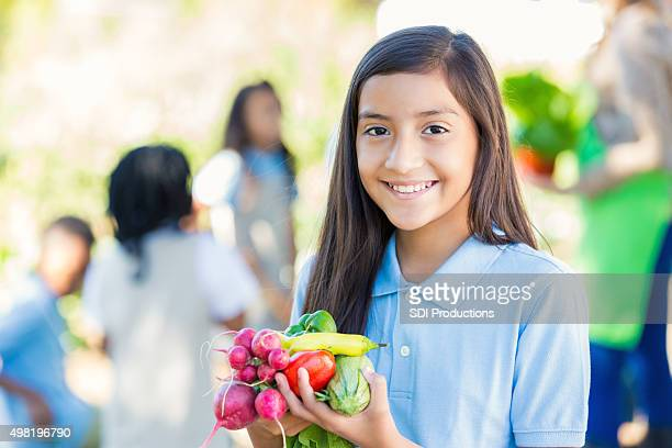 Student holding vegetables she picked from garden during field trip