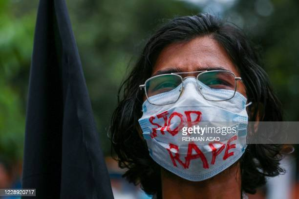 Student holds a black flag to protest against an alleged gang-rape and stripping and torturing of a woman in the southern district of Noakhali during...