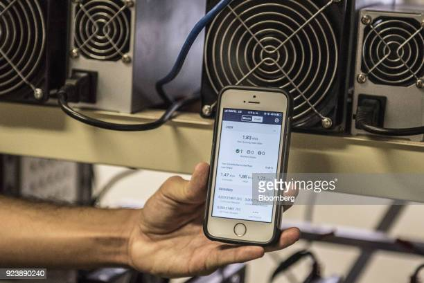 A student holds a mobile device displaying the performance of mining rigs inside the cryptocurrency mining farm and school at the Ministry of Youth...