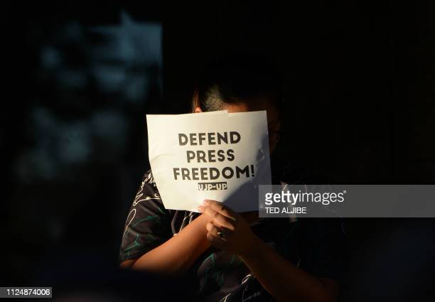 Student holds a placard during a protest at the state university grounds in Manila on February 14 in support of CEO of Rappler, Maria Ressa, who was...