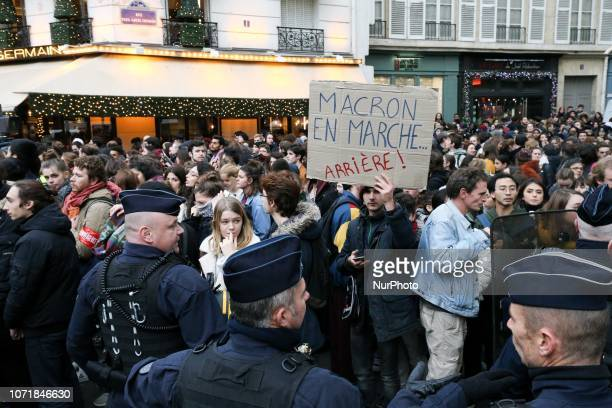 A student holds a placard reading « Macron in reverse » during a demonstration boulevard SaintGermain Paris France on December 11 to protest against...
