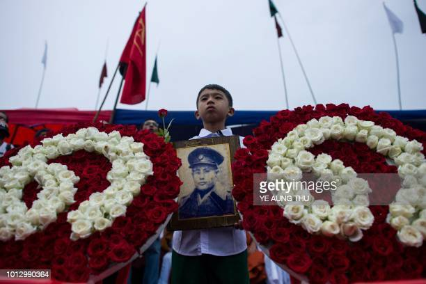 TOPSHOT A student holds a portrait of General Aung San during a ceremony to mark the 30th anniversary of the 8888 uprising in front of city hall in...
