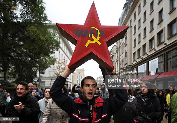 A student holds a red star symbol of the former communist regime during an antigovernment protest in center of Sofia on November 15 2013 The protest...