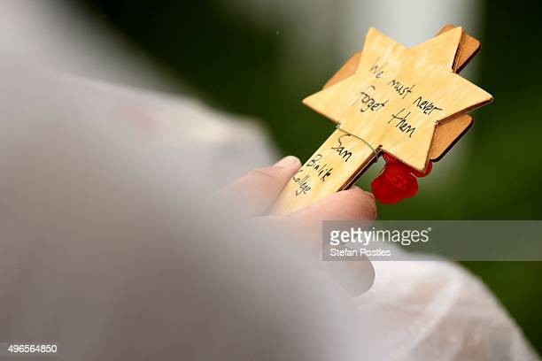 A student holds a sign made to lay at the foot of the Stone of Remembrance during the Remembrance Day Ceremony at the Australian War Memorial on...