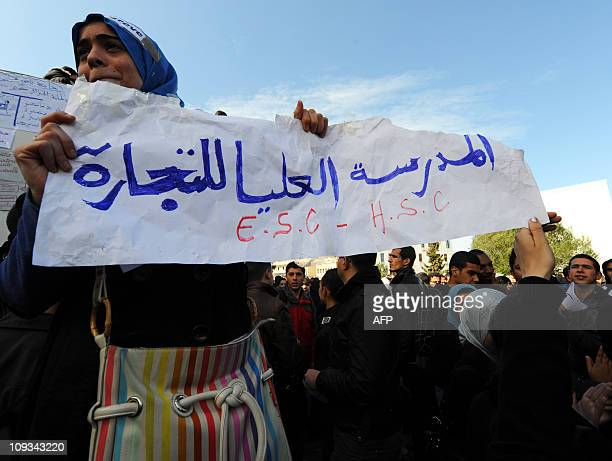 A student holds a sign reading 'buisness school' during a protest where students demanded the government to repeal a decree setting a benefit scheme...