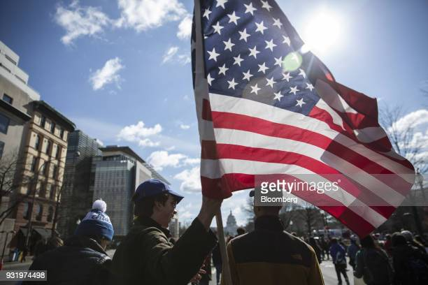 A student holds an American flag while marching towards the US Capitol during the ENOUGH National School Walkout rally in Washington DC US on...