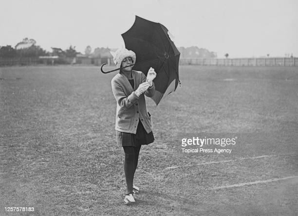 A student holds an umbrella with her mouth as she puts gloves on during the Sports Day of Ashford County Schools Middlesex UK July 1923