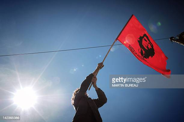 A student holds up a flag featuring revolutionnary legend Ernesto Che Guevara during a demonstration of some 40000 people 04 April 2006 in Lyon...